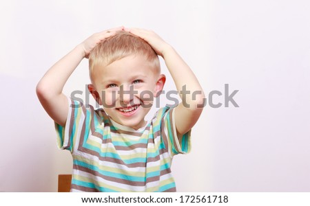 Portrait of surprised excited emotional blond boy child kid at the table interior. Emotions.