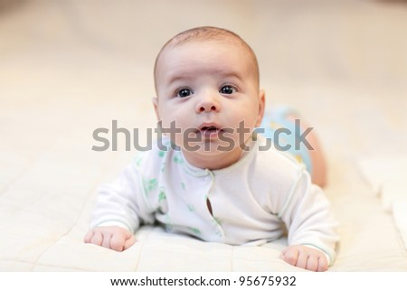 Portrait of surprised infant on the bed at home