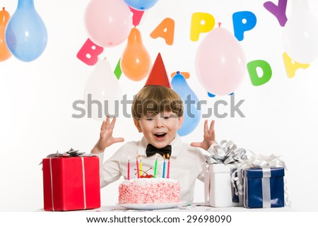 Portrait of surprised lad keeping his hands above birthday cake with burning candles and looking at it astonishingly