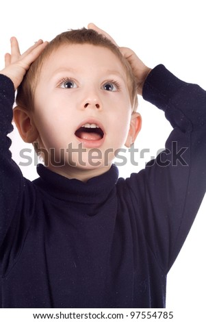Portrait of surprised little boy with blond hair covering his mouth by hands