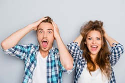 Portrait of surprised man and woman screaming and touching hair
