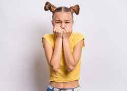Portrait of surprised or shocked teen girl, on gray background. Funny child looking at camera with hands on mouth, biting nails. Beautiful caucasian teenager with opening wide eyes looking stressed