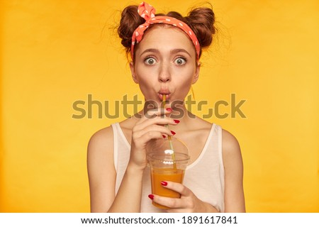 Portrait of surprised, red hair girl with red doted hairband. Shocked with taste, make a sip. Wearing white shirt and holding her smoothie. Watching at the camera isolated over yellow background Stock photo ©