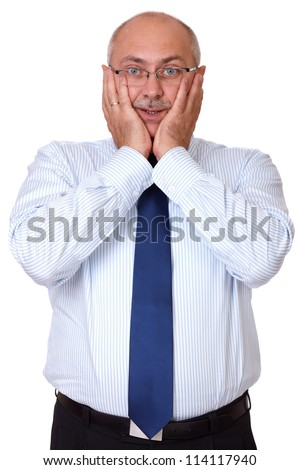Portrait of surprised senior businessman in blue shirt standing with hands on face, isolated on white