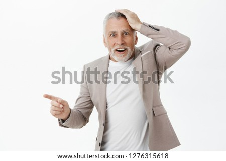 Portrait of surprised senior father being amazed and impressed holding hand on head from surprise and amazement pointing left questioned at stunning and intriguing copy space posing in formal suit