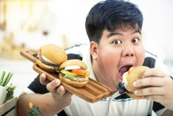Portrait of surprised young asian fat man looks exciting with hamburger on his hands