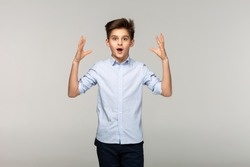Portrait of surprised young boy in blue shirt with short hair, studio portrait on white background