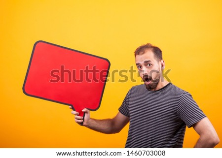 Portrait of surprised young man looking at the camera and holding a news board over yellow background. Copyspace available.