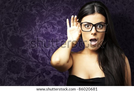 portrait of surprised young woman hearing a sound against a vintage wall