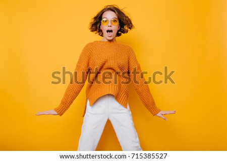 Portrait of surprised young woman in white pants jumping in front of yellow wall. Indoor portrait of curly lady in sunglasses fooling around in studio.