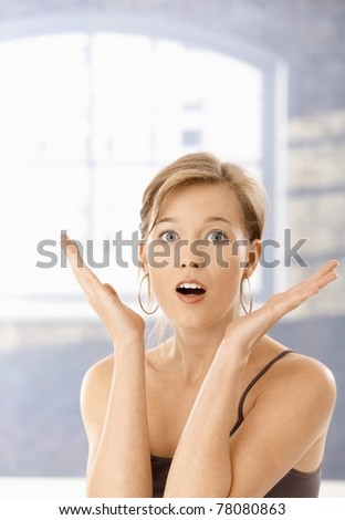 Portrait of surprised young woman, looking at camera with open mouth.?