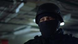Portrait of SWAT member in helmet standing in dark building. Masked military soldier posing at camera. Special operation participant waiting for instructions during mission