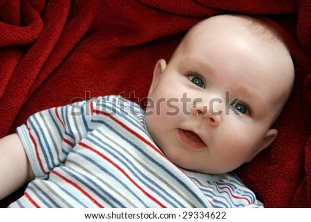 Portrait of sweet baby. Four months old baby boy lying on red blanket.