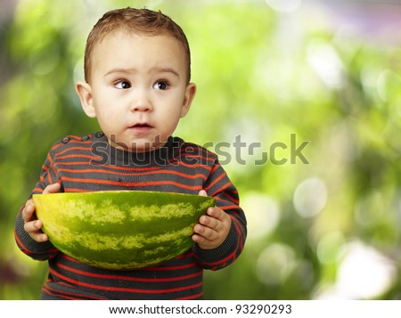 portrait of sweet kid holding a big watermelon against a nature background