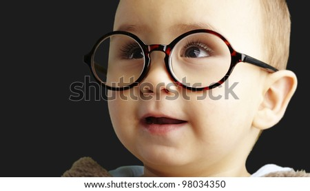 portrait of sweet kid wearing round glasses over black background