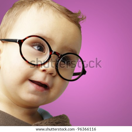 portrait of sweet kid wearing round glasses over pink background