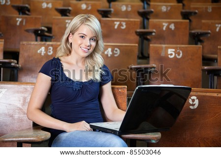 Portrait of sweet young college girl using laptop in university lecture hall
