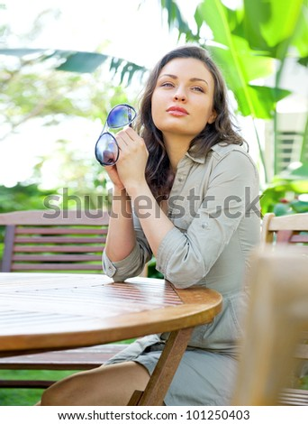 Portrait of sweet young woman sitting outdoors at backyard of her house and smiling