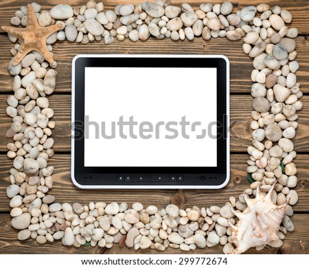 Portrait of tablet PC in the middle of frame from sea shells and stones. Vintage greeting card with shells and starfishes and place for text.