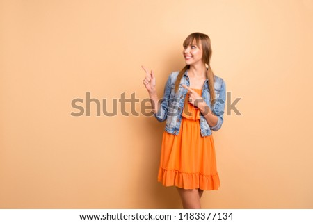 Portrait of tails charming promoter attractive look ads adverts choice decisions wear fashionable clothing orange skirt dress modern she her isolated beige background