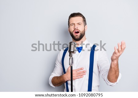 Portrait of talented attractive singer with bristle stubble in elegant classic outfit, singing hit with open mouth in microphone gesture with hand isolated on grey background #1092080795