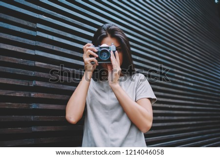 Portrait of talented brunette hipster girl posing and making pictures using vintage equipment, young professional female photographer 20 years old looking at camera and taking images outdoors