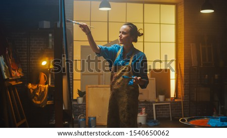 Portrait of Talented Female Artist Working on a Modern Abstract Oil Painting, Gesturing with Broad Strokes Using Paint Brush. Dark Creative Studio Large Picture Stands on Easel Illuminated. Low Angle