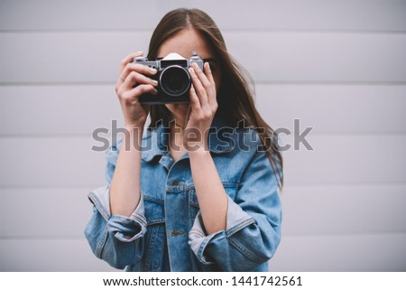 Portrait of talented hipster girl posing near wall while making pictures using obsolete vintage camera, young professional female photographer in leans jacket standing outdoor photographing