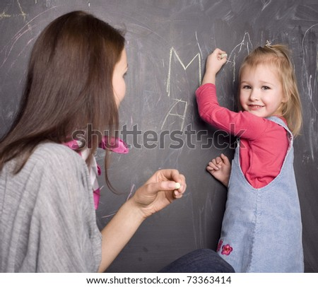 portrait of teacher and little student, mother and daughter near blackboard - stock photo