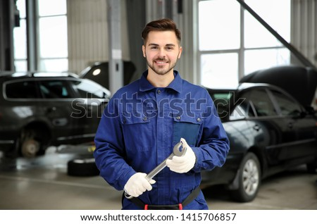 Portrait of technician with wrench at automobile repair shop #1415706857