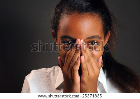 Portrait of teen african girl covering her face