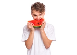 Portrait of teen boy eating ripe juicy watermelon and smiling. Cute caucasian young teenager with slice healthy watermelon. Funny happy child wearing white t-shirt, isolated on white background.