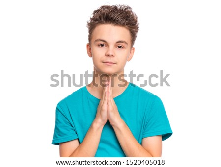 Portrait of teen boy praying, isolated on white background. Cute caucasian teenager with hands folded in prayer hoping for better. Child asking God for good luck, success or forgiveness. Stock foto ©