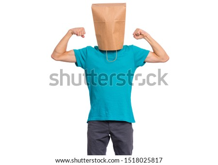 Portrait of teen boy with paper bag over head raised his hands and shows biceps, isolated on white background. Child shows biceps.