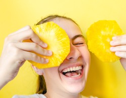 Portrait of teen girl smiling and laughing holding two round slices of pineapple before her face against yellow background. Summer food, summertime joy, vacation, holidays, minimal monochrome concept.