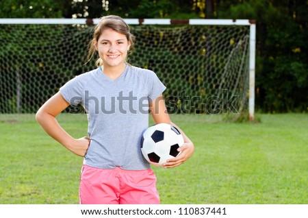 Portrait of teen girl soccer player on field