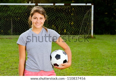 Portrait of teen girl soccer player on field