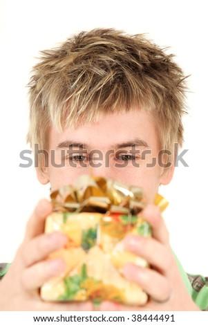 Portrait of teenage boy holding Christmas gift, studio shot