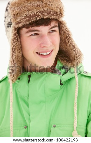 Portrait Of Teenage Boy In Snow Wearing Fur Hat