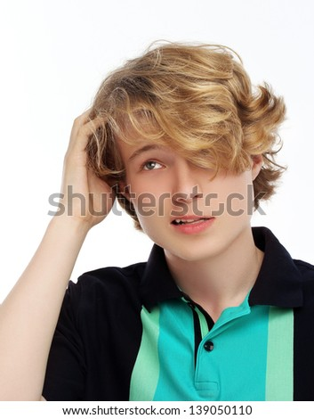 Portrait of teenage boy thinking, looking at camera and scratching his head.