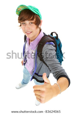 Portrait of teenage boy with backpack looking at camera and showing thumb up - stock photo