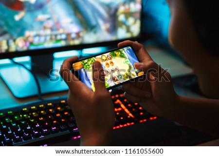 Photo of  Portrait of teenage gamer boy playing video games on smartphone and computer in dark room wearing headphones and using backlit colorful keyboard