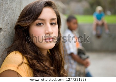 Portrait of teenage girl hanging out with friends outdoors at camera