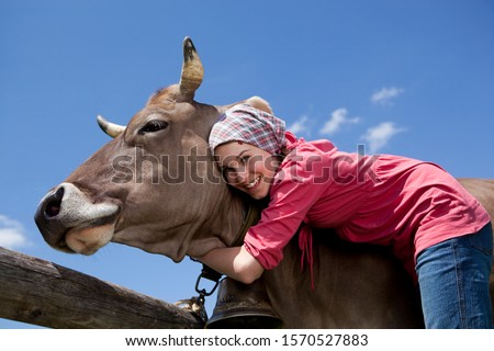 Portrait of teenage girl hugging cow