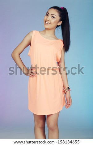 Portrait of teenage girl in coral colored dress, studio