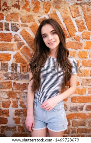 Portrait of teenage girl standing over brick wall and smiling to a camera. #1469728679
