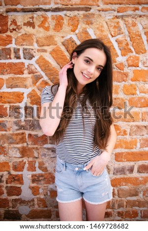 Portrait of teenage girl standing over brick wall and smiling to a camera. #1469728682