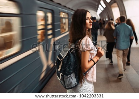 Portrait of teenage girl with backpack waiting the train in subway. #1042203331