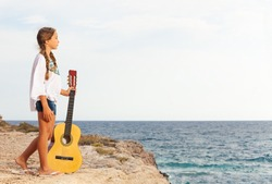 Portrait of teenage girl with guitar standing on the edge of a cliff and looking at the sea
