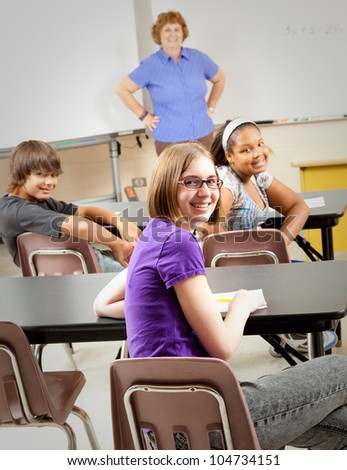 Portrait of teenage students and their teacher in the classroom.  Focus on the girl in the front with glasses.